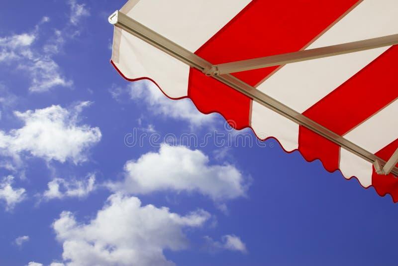 Toldo sobre el cielo azul asoleado brillante fotos de archivo