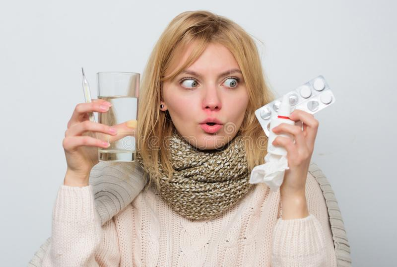 Tolerating the drug well. Ill woman treating symptoms caused by cold or flu. Unhealthy woman holding pills and water. Glass. Cute sick girl taking anti cold royalty free stock photography