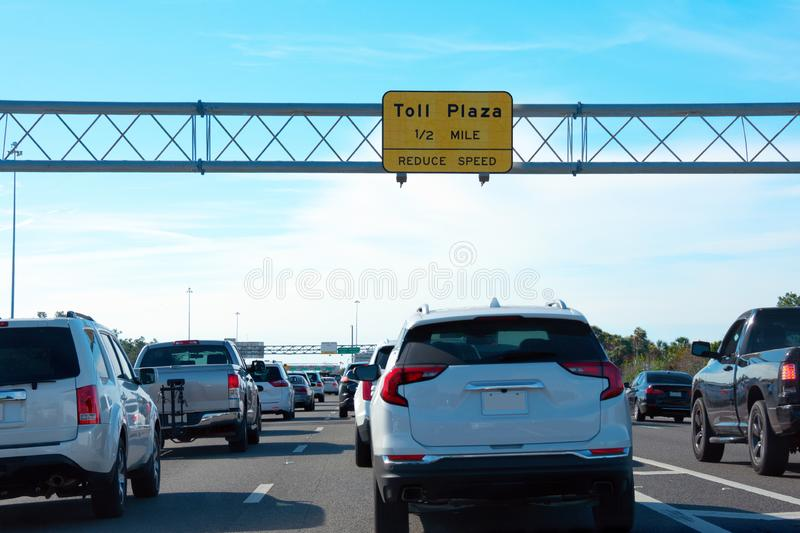 Toll Plaza 1/2 MILE yellow sign on overhead metal tri-chord truss with toll booths in the far distance and cars in traffic jam stock images
