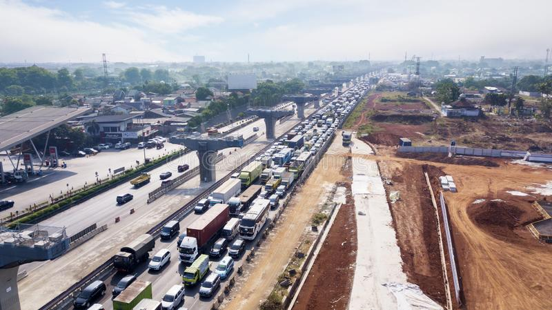 Toll road with hectic traffic and construction pilings. West Java, Indonesia - October 10, 2018: Aerial view of Jakarta-Cikampek toll road with hectic traffic stock photography