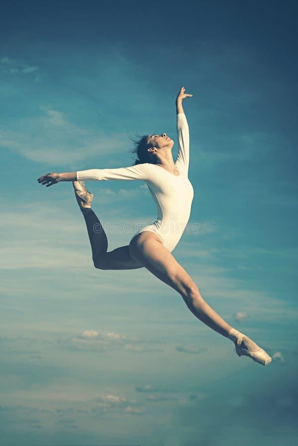 Tolleranza in ogni movimento Arte di pratica di balletto classico La ballerina che salta sul cielo blu Danzatore di balletto sveg fotografie stock