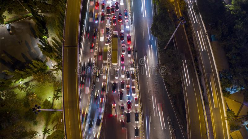 Tollway with light trails at night. Aerial view of hectic traffic on the tollway with light trails at night in Jakarta downtown stock photography