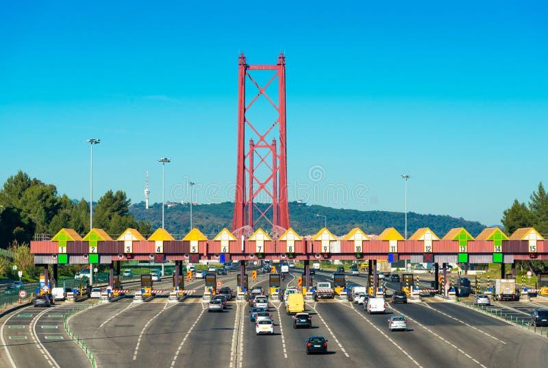 Tolpost bij de ingang aan 25ste April Bridge tussen Lissabon en Almada, Portugal Auto's die door publieke telefooncel overgaan stock fotografie