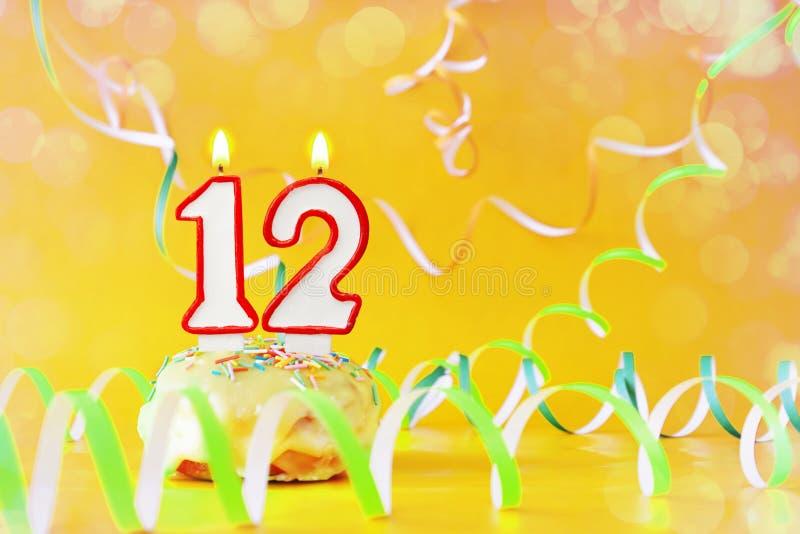 Tolv år födelsedag Muffin med brinnande stearinljus i form av nummer 12 royaltyfri foto