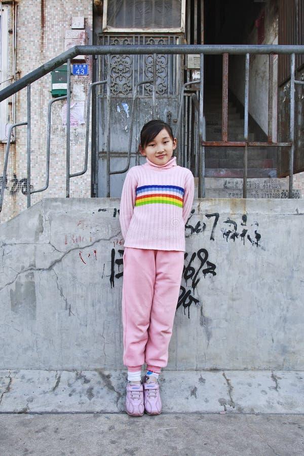 Tolv år gamla Wang Ping framme av gammal hyreshus, Qingdao, Kina royaltyfri foto