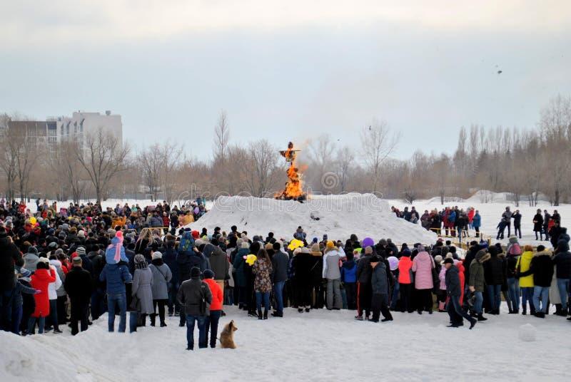 Celebration of Maslenitsa: people are watching the moment of burning stuffed Maslenitsa. Tolyatti, Samara region, Russia - March 10, 2019: Celebration of stock photos