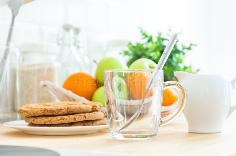 Tom Ñ- upp, mjölkar tillbringaren, kakor och frukt på köksbordet Framställning bra eller sund morgonen av den frukost, arkivfoto