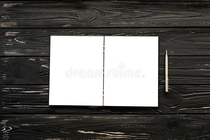 Tom öppen anteckningsbok- och silverpenna på den svarta träbakgrunden royaltyfria bilder