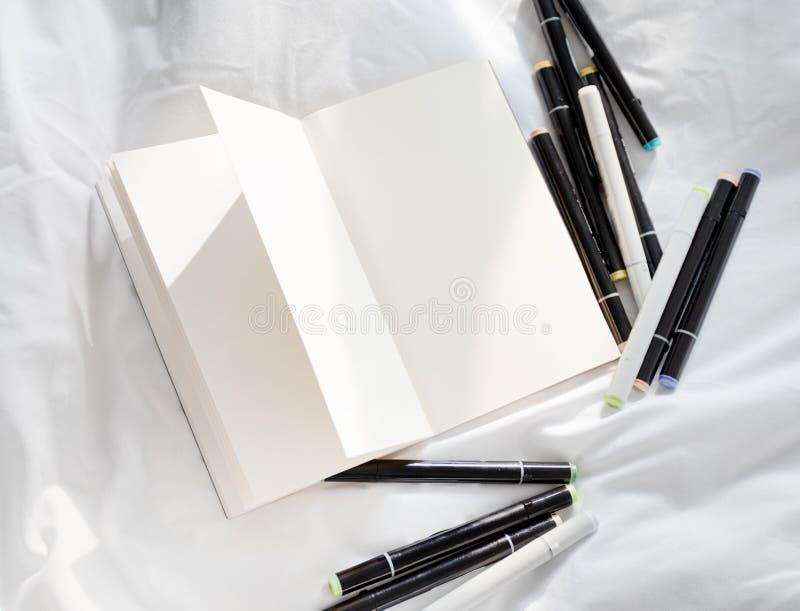 Tom öppen dagbok på en vit säng med högen av pennor royaltyfri bild