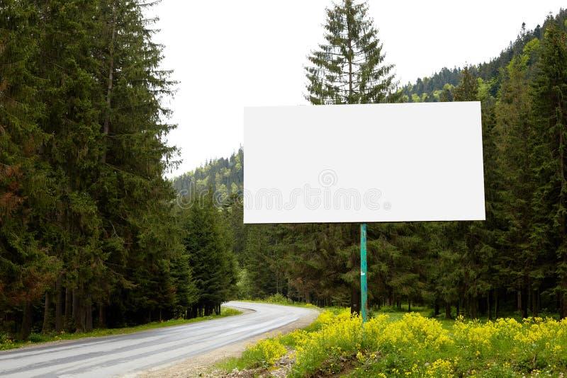 Tom affischtavla eller stort bräde på sida av vägen med den gröna skogen och kullar på bakgrund Annonsera upp mellanrumet som är  royaltyfri foto