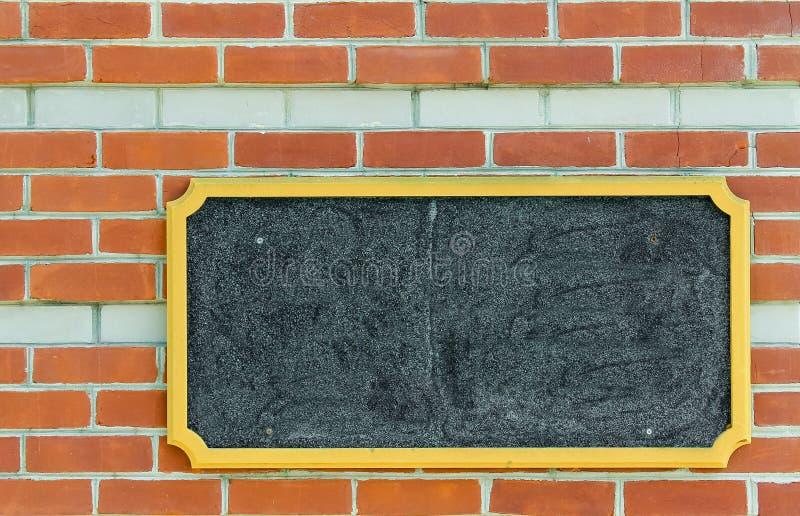 Tom affischtavla på en tegelstenvägg arkivbild