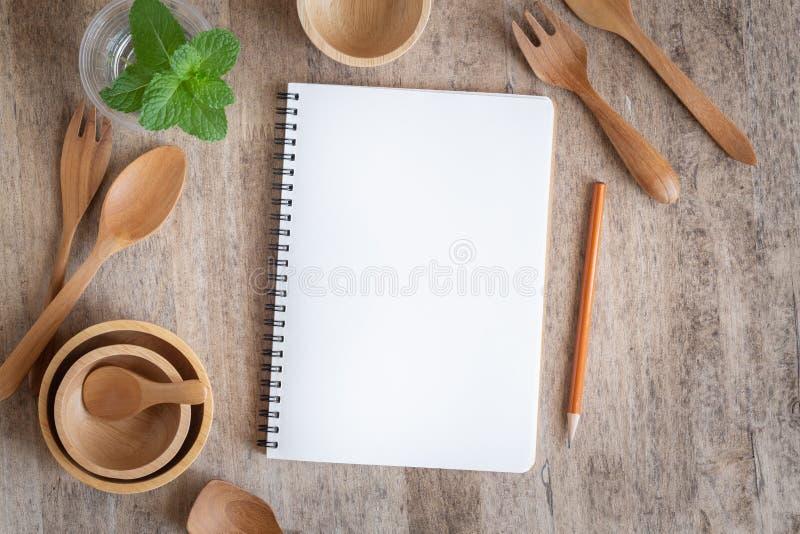 Tom anteckningsbok f?r textanm?rkning p? tr?tabellbakgrund P? tr? ha den skedgaffeln och blyertspennan royaltyfri bild