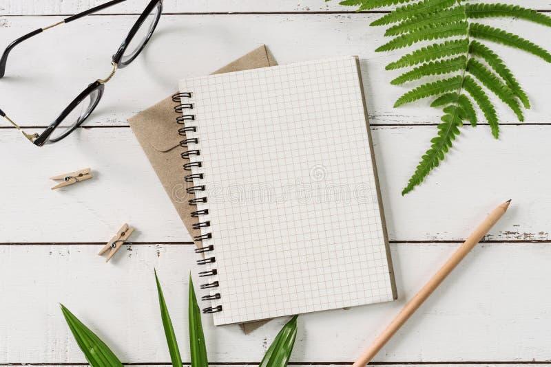 Tom anteckningsbok med gräsplansidor på den vita trätabellen fotografering för bildbyråer