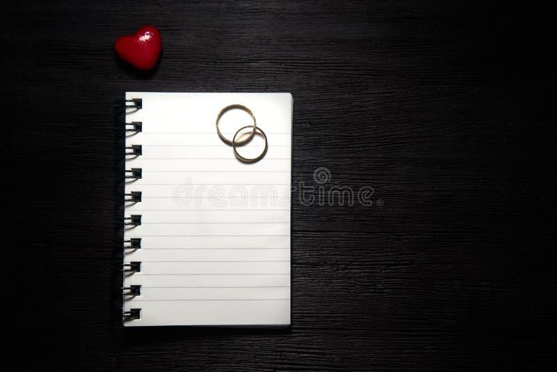 Tom anteckningsbok med hjärta och vigselringar på svart bakgrund arkivbilder