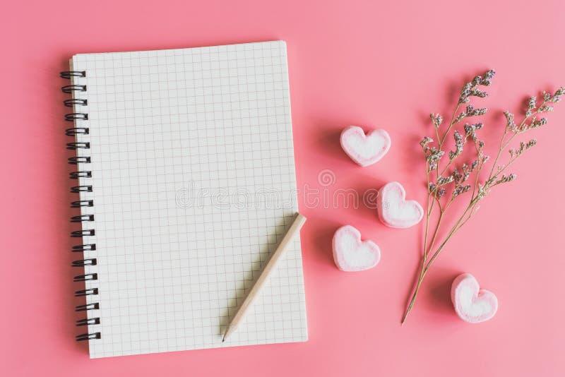 Tom anteckningsbok med hjärtaformgodisen och den torkade blomman arkivfoto