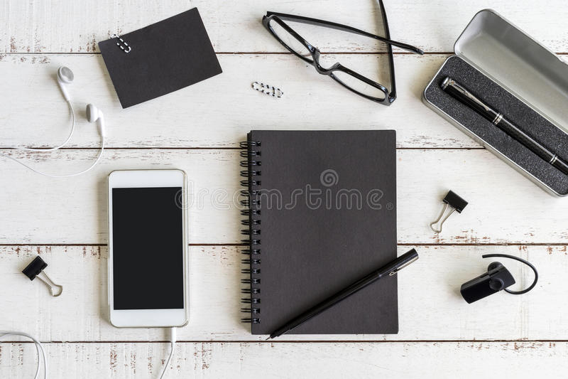 Tom anteckningsbok med mobiltelefonen på skrivbordkontor royaltyfri bild