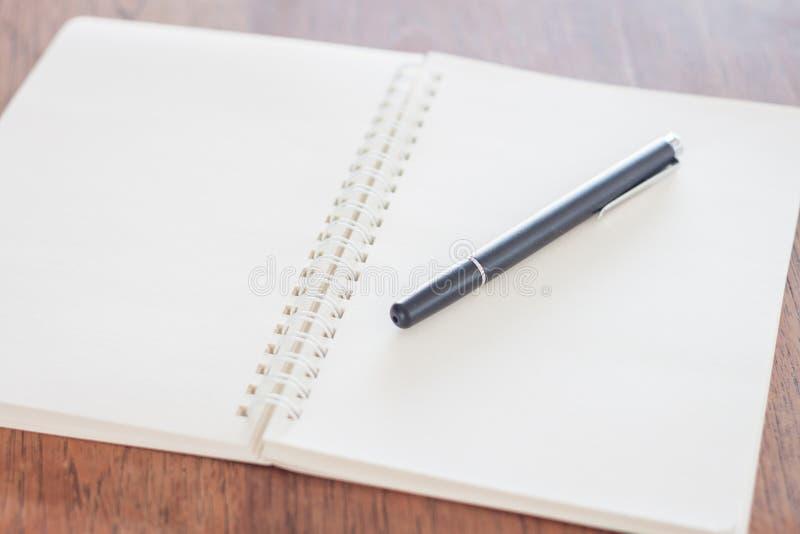 Tom anteckningsbok med pennan på trätabellen arkivbilder