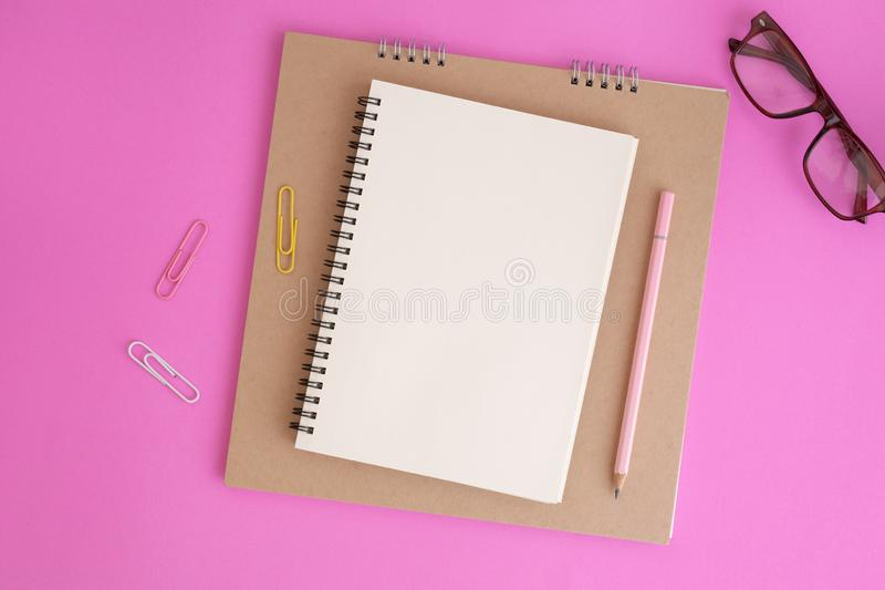 Tom anteckningsbok och blyertspenna på rosa bakgrund, plant lekmanna- foto av anteckningsboken för ditt meddelande arkivfoton