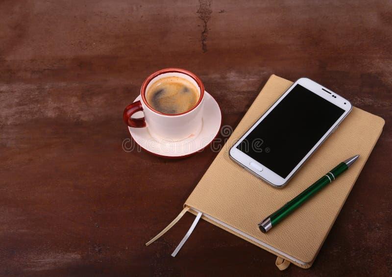 Tom anteckningsbok- och bollpenna med en kopp kaffe, telefon av kontorsskrivbordet äganderätt för home tangent för affärsidé som  royaltyfri foto