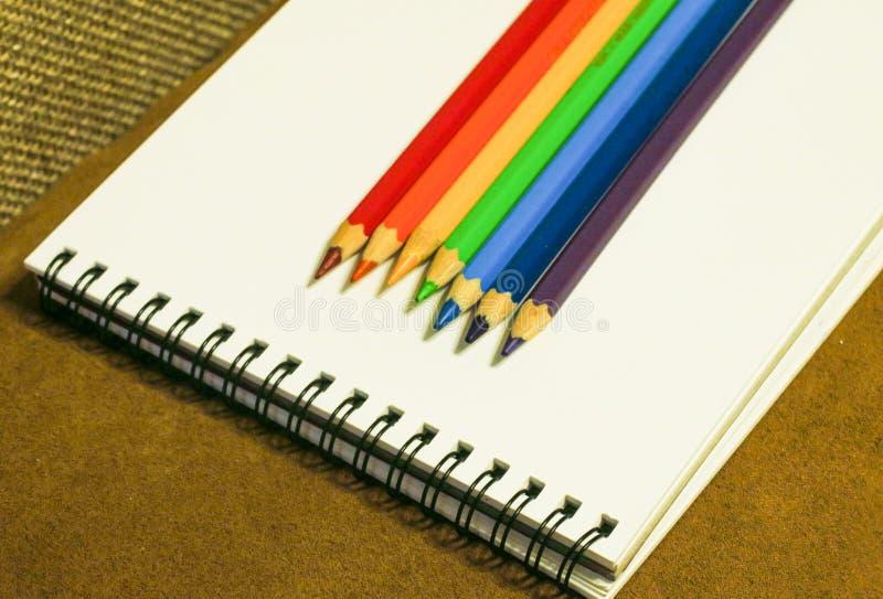 Tom anteckningsbok och färgrika blyertspennor på brun bakgrund, royaltyfria bilder