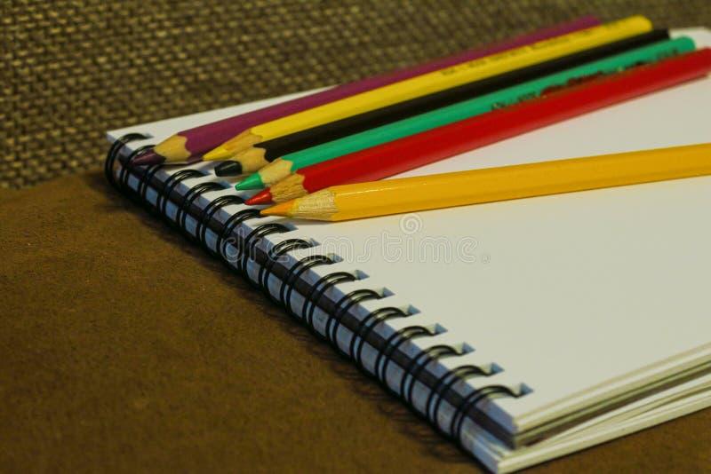 Tom anteckningsbok och färgrika blyertspennor på brun bakgrund, royaltyfria foton