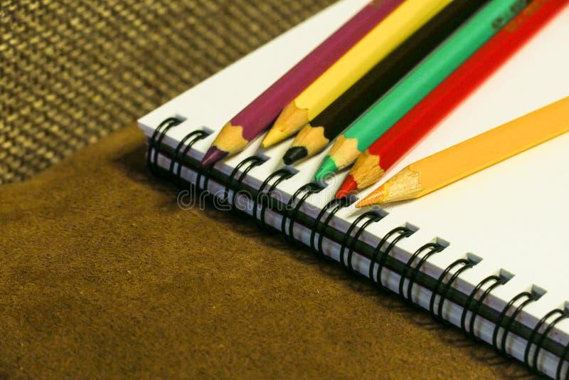 Tom anteckningsbok och färgrika blyertspennor på brun bakgrund, arkivfoto