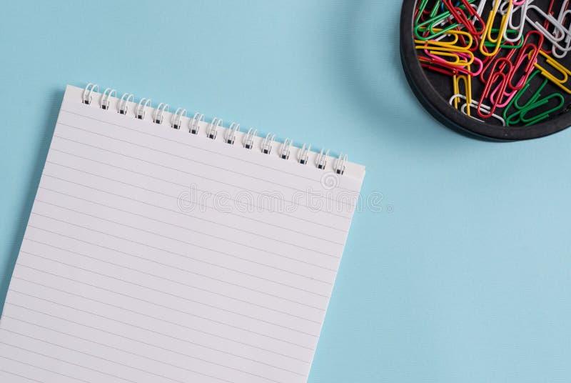 Tom tom anteckningsbok och gem som förläggas ovanför pastellfärgtabellen Anmärkningspapper plus den stationära pinnen till modern arkivfoto