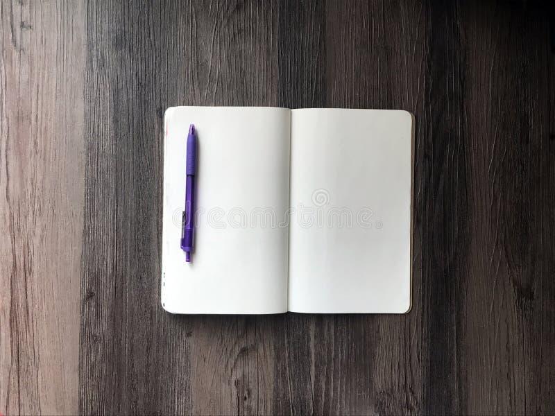 Tom anteckningsbok- och lilapenna arkivfoton