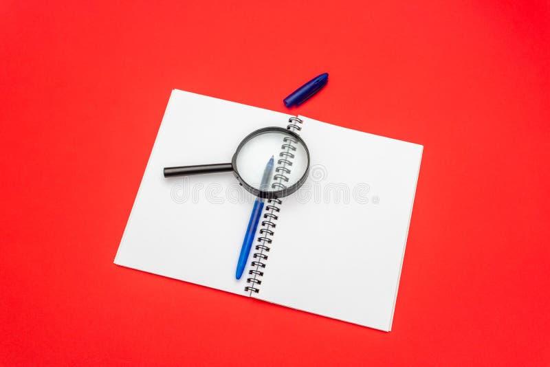 Tom anteckningsbok och penna på röd bakgrund F?rstoringsglas ?verst av notepaden arkivfoton