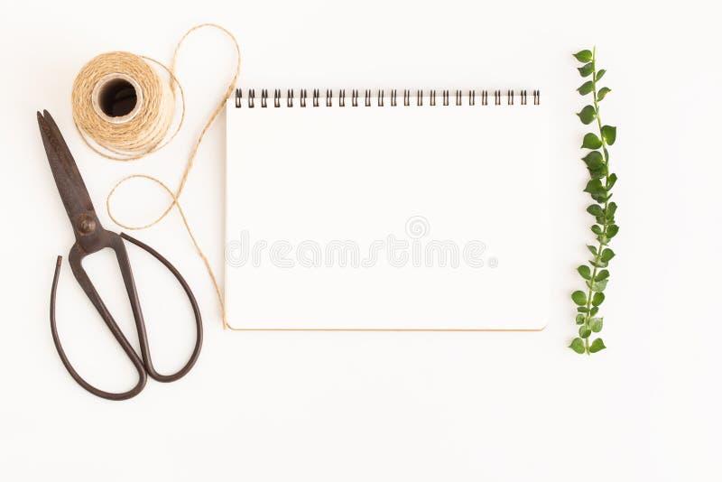 Tom anteckningsbok och sax på vit bakgrund, bild för bästa sikt av den vita anteckningsboken och tomt utrymme för text arkivfoton
