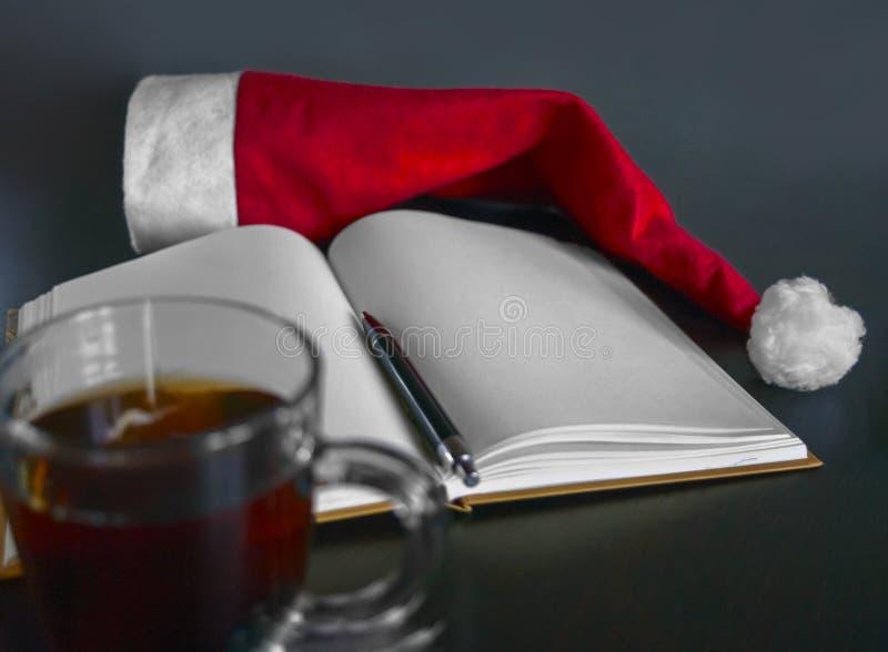 Tom anteckningsbok, svart penna, röda jultomten hatt, kopp te på en trätabell Upplösningar för ` s för nytt år Ställa in mål som  royaltyfri fotografi