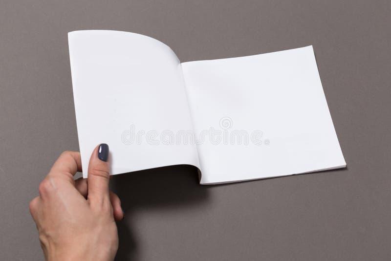 Tom anteckningsbokmodell med handen på räkningen royaltyfria foton