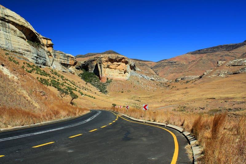 Tom asfaltväg i Golden GateSkotska högländerna nationalpark, Sydafrika arkivfoton