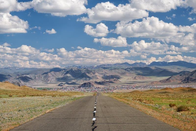 Tom asfaltväg i Mongoliet med den mongolian staden Bayan-Olgii (Bayan-Ulgii eller Ulgii) på bakgrund royaltyfri bild