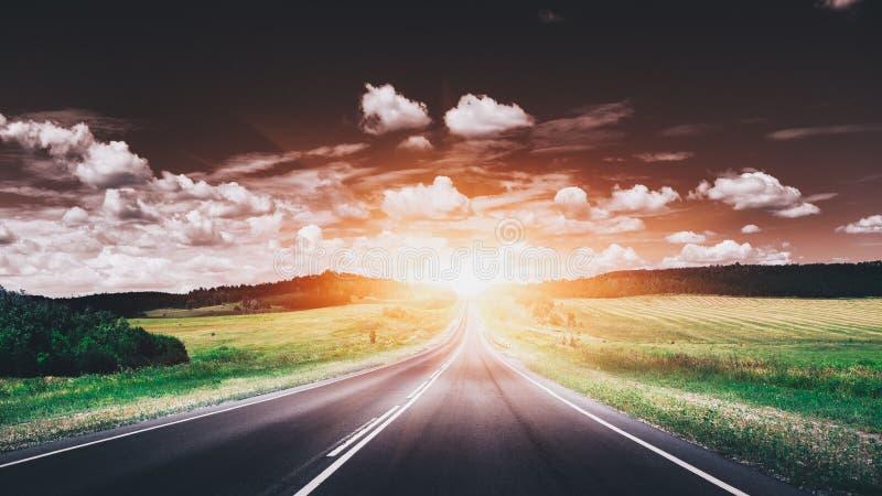 Tom asfaltväg på solnedgången härlig liggandenatur royaltyfri bild