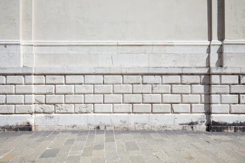 Tom belagd med tegel stentrottoar och vit forntida vägg royaltyfri bild