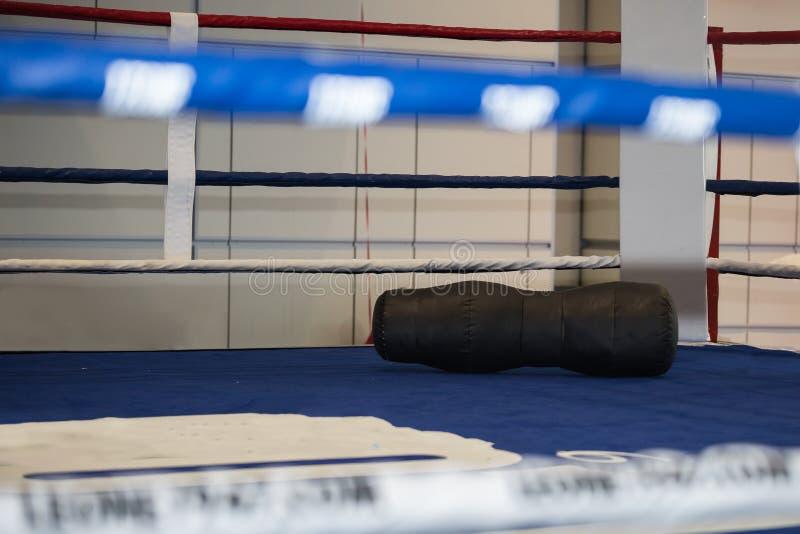 Tom boxningsring med den svarta stansa påsen på jordningen royaltyfri foto