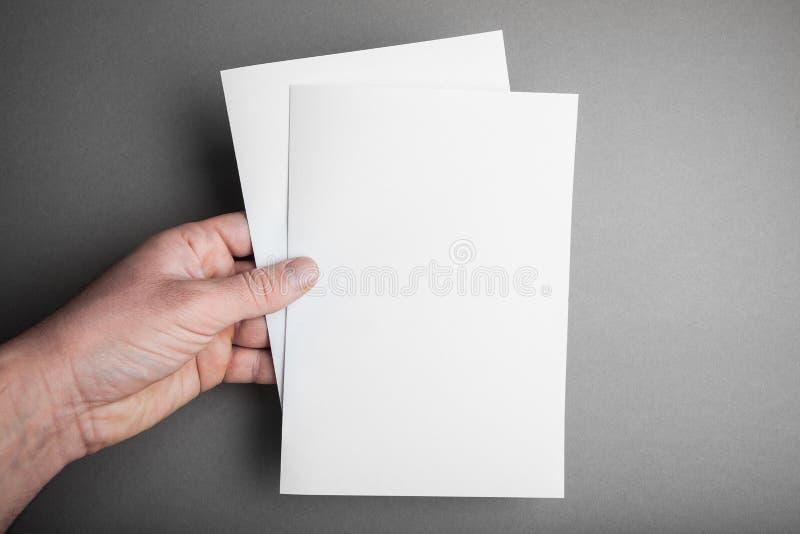 Tom broschyrtidskrift som isoleras på grå färger, med urklippbanan i manhand arkivfoton