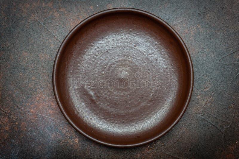 Tom brun platta som är keramisk på en mörk bakgrund med en kniv och en gaffel royaltyfria foton