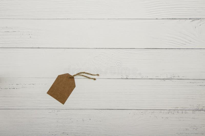 Tom brun prislapp på på vit träbakgrund ovanför sikt Prislapp eller etikett för mellanrumsbruntpapp på vitt b arkivbild