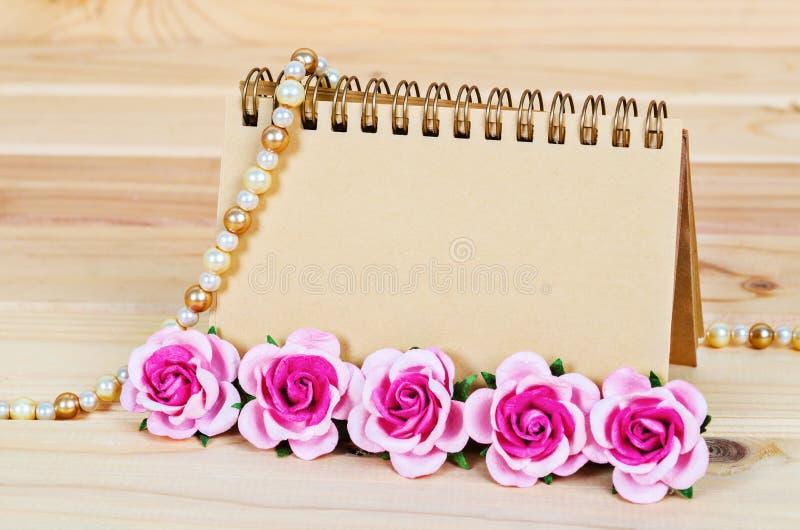 Tom brun tom anteckningsbok med rosa rosor på träbakgrund fotografering för bildbyråer