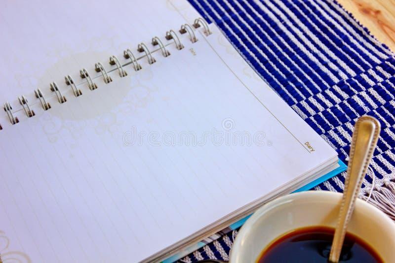 Tom dagbok med svart kaffe royaltyfri foto