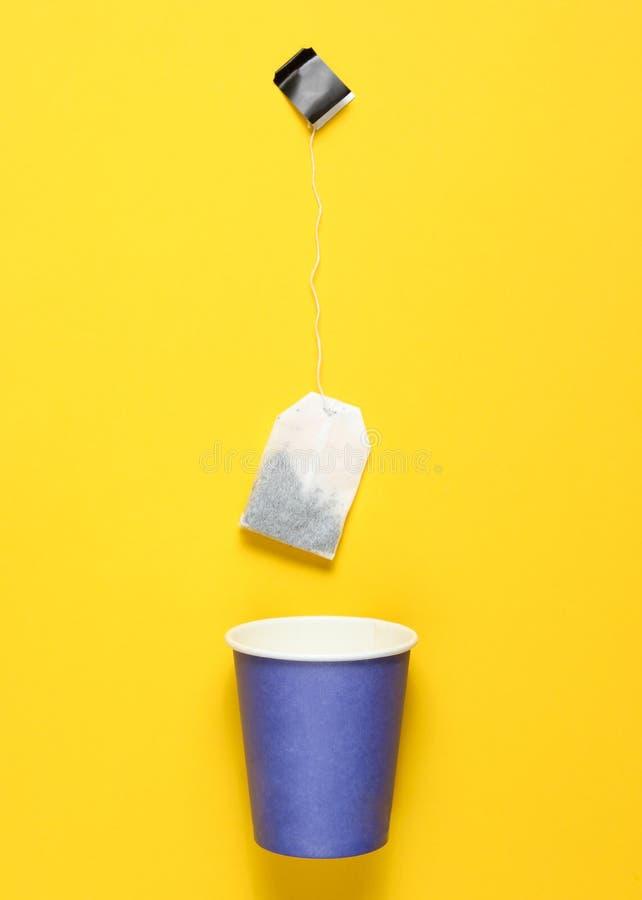 Tom disponibel pappers- kopp för te, tepåse på en gul bakgrund, bästa sikt, minimalism royaltyfri foto