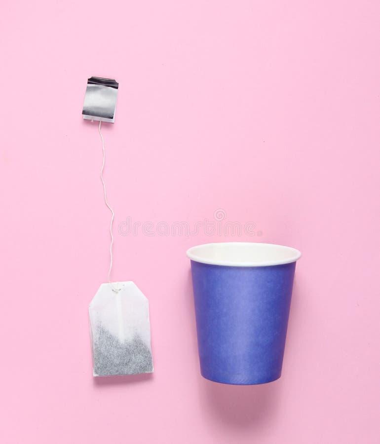 Tom disponibel pappers- kopp för te, tepåse på rosa pastellfärgad bakgrund, bästa sikt, minimalism royaltyfria bilder
