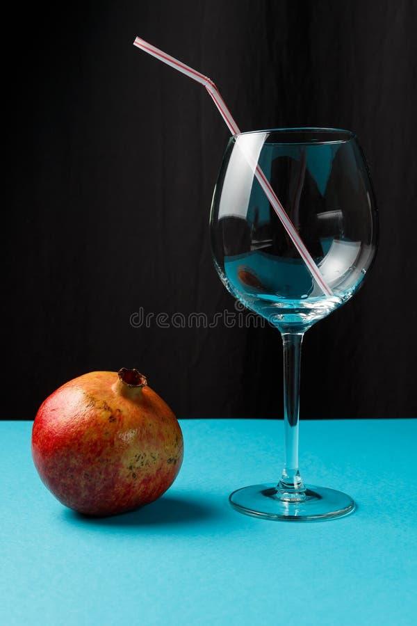 Tom exponeringsglas och granatäpple på en blå bakgrund Vitaminer och mineraler arkivbild