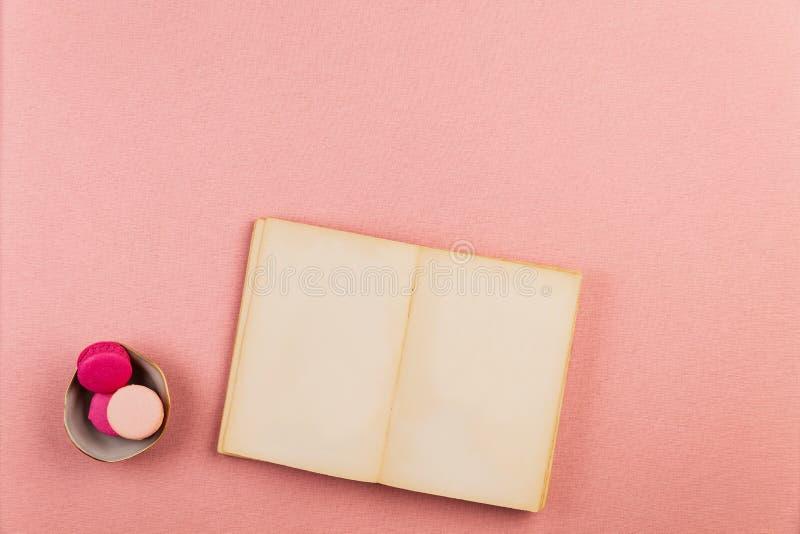 Tom forntida liten bok som är öppen med rosa franska macarons, över en rosa bordduk med copyspace för anmärkningar eller konst fotografering för bildbyråer