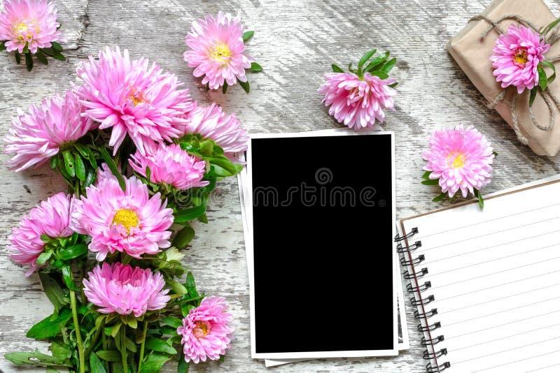 Tom fotoram och pappersanteckningsbok med rosa asterblommor och gåvaasken royaltyfria foton