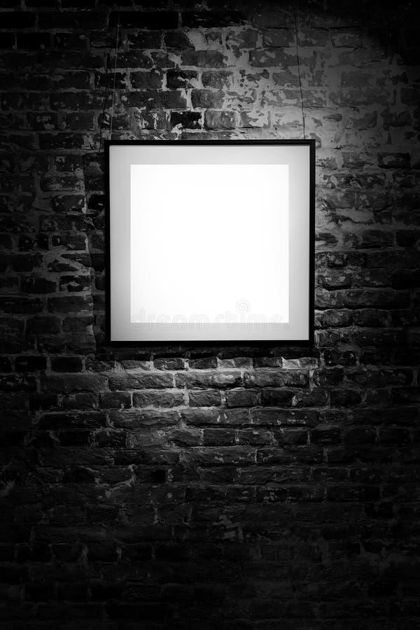 Tom fyrkantig ram på den svarta tegelstenväggen Affisch för tomt utrymme eller konstram som väntar för att fyllas Fyrkantig svart royaltyfria foton