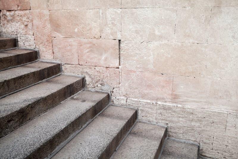 Tom gammal konkret trappa nära stenväggen arkivfoton