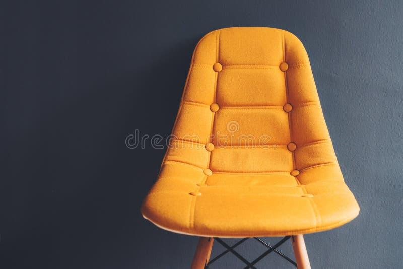 Tom generisk gul stol mot den gråa väggen för väntande rum arkivfoto